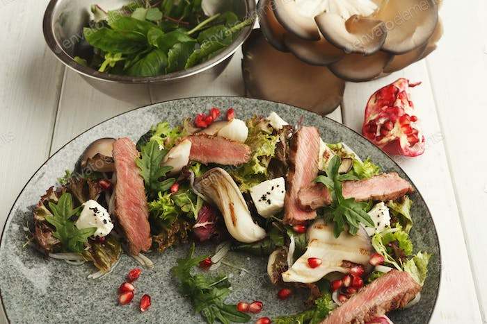 Warm mix salad with duck meat and mushrooms. Modern restaurant dish