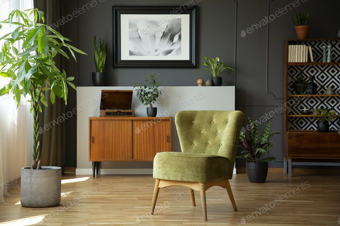 Green chair next to plant in grey living room interior with post