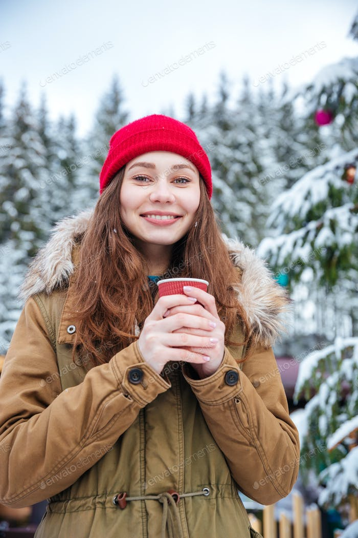 Woman drinking coffee near decorated christmas tree in winter forest