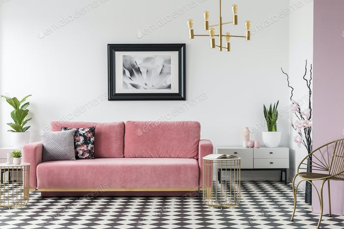 Pink couch next to cabinet with plant in living room interior wi