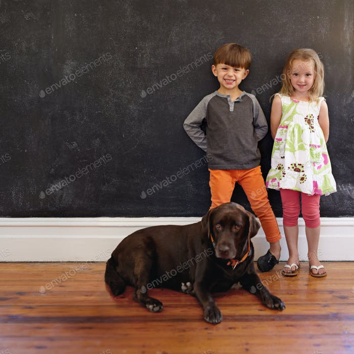 Smiling little children with their dog at home