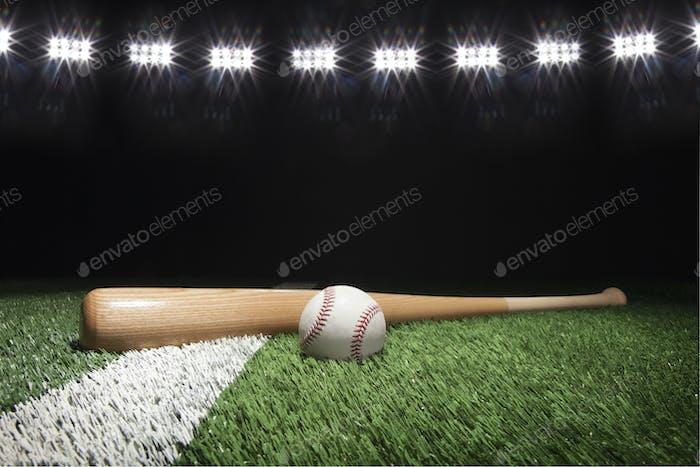 Baseball and bat on field under stadium lights at night