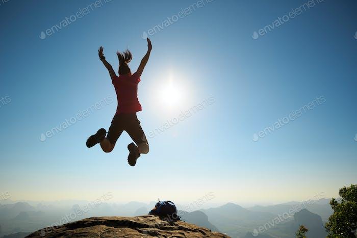 Jumping on sunrise mountain top