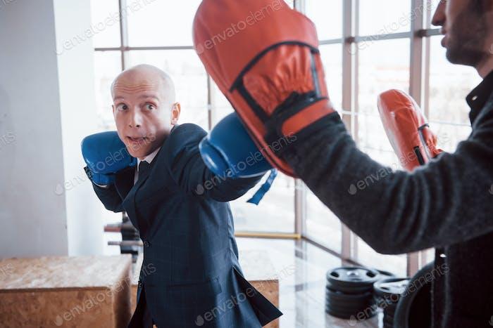 Ein wütender kahler Geschäftsmann schlägt eine Boxbirne in der Turnhalle. Konzept des Wutmanagements