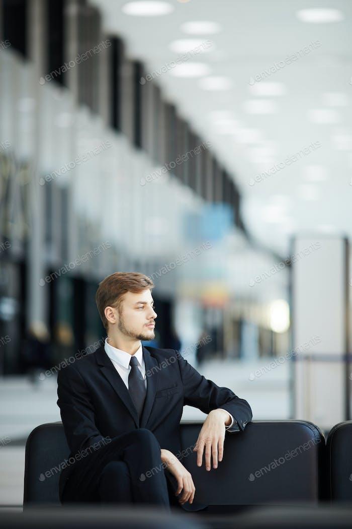 Молодой бизнесмен ждет в аэропорту