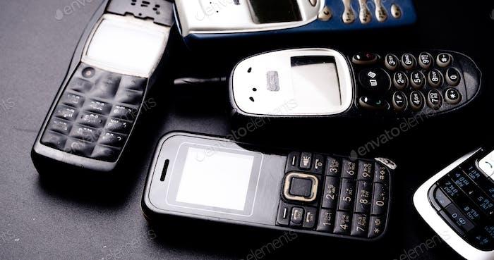 Heap of vintage mobilephones on a black background.