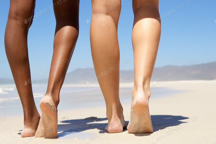 Low angle two women walking barefoot
