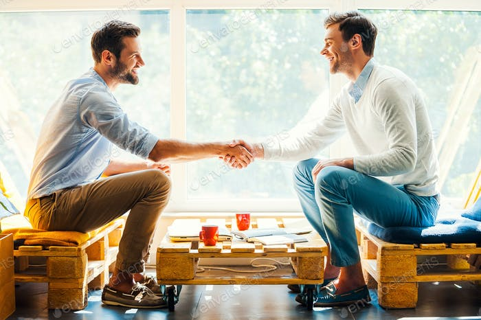Männer schütteln die Hände.