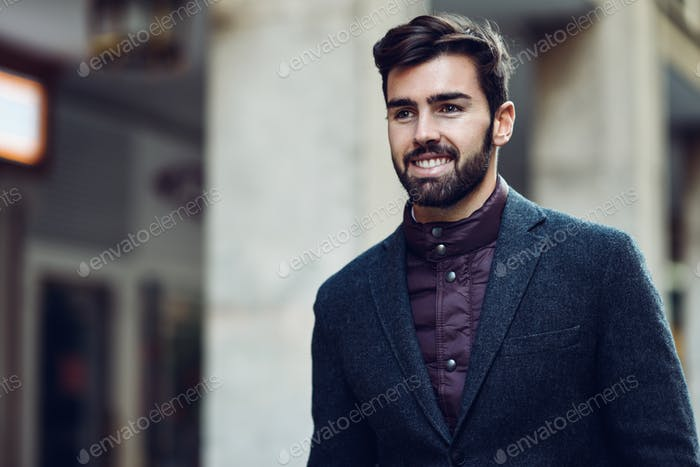 Young bearded smiling man wearing british elegant suit in the st