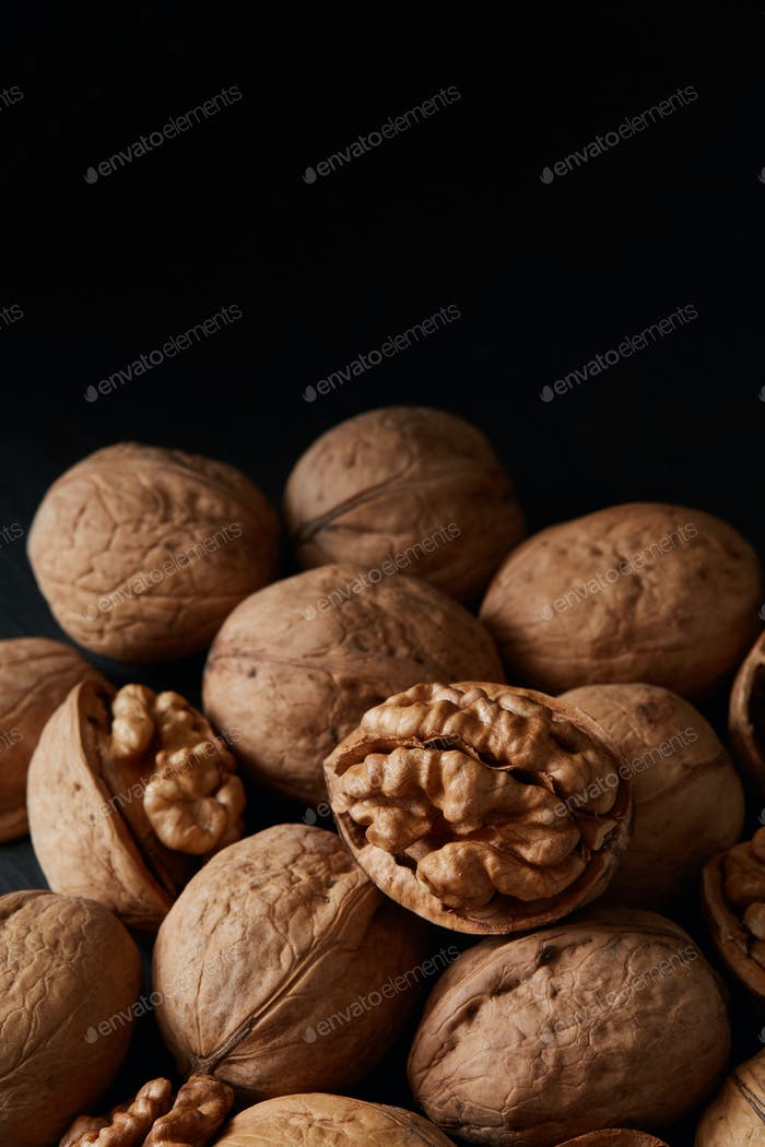 Walnuts and kernels on a black backdrop