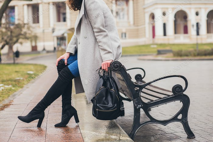young beautiful woman walking in the city street in grey coat