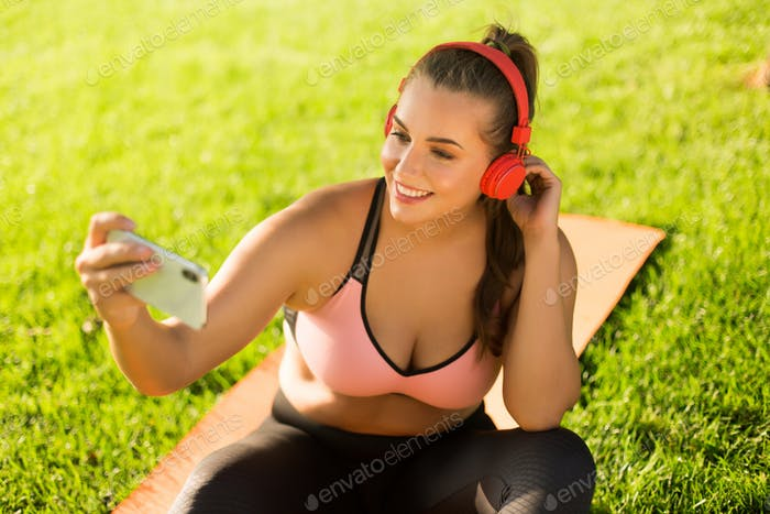Young pretty smiling plus size woman in pink sporty top and legg