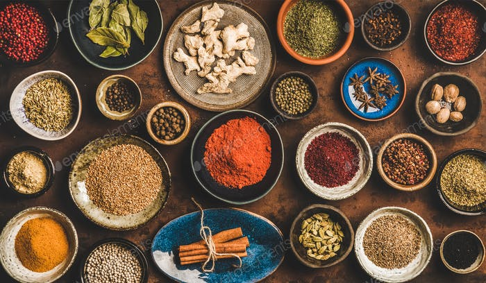 Flat-lay of different spices in bowls over rusty background