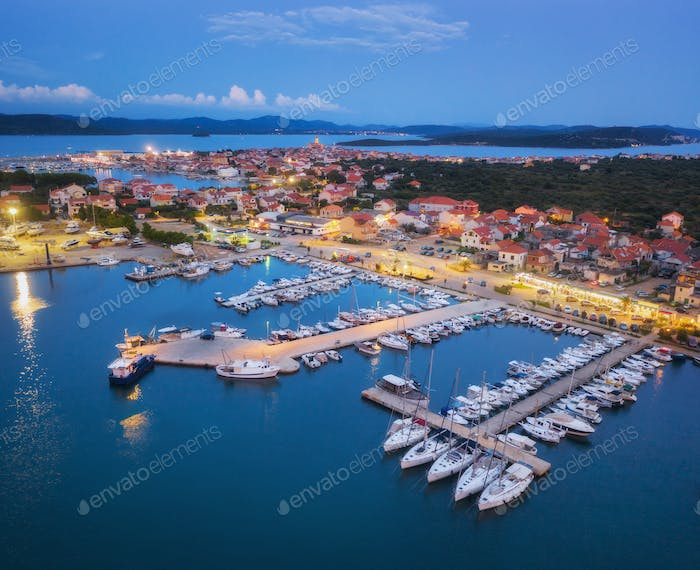 Aerial view of boats and yachts in port and city at night