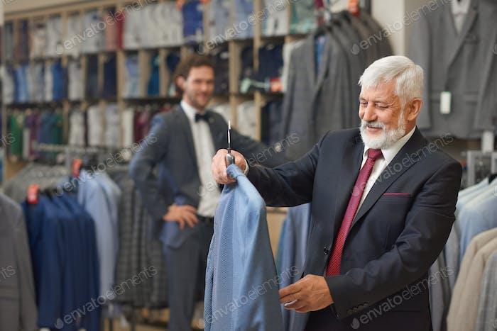 Guapo senior con el pelo gris eligiendo ropa elegante