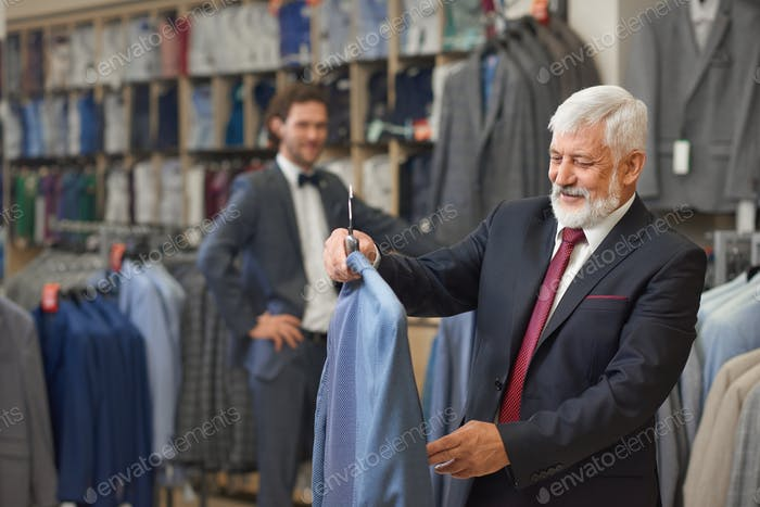 Handsome senior with grey hair choosing elegant clothes