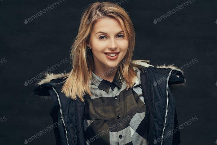Porträt eines blonden Mädchens in einer Winterjacke und Fleece-Hemd, stehend in einem Studio.