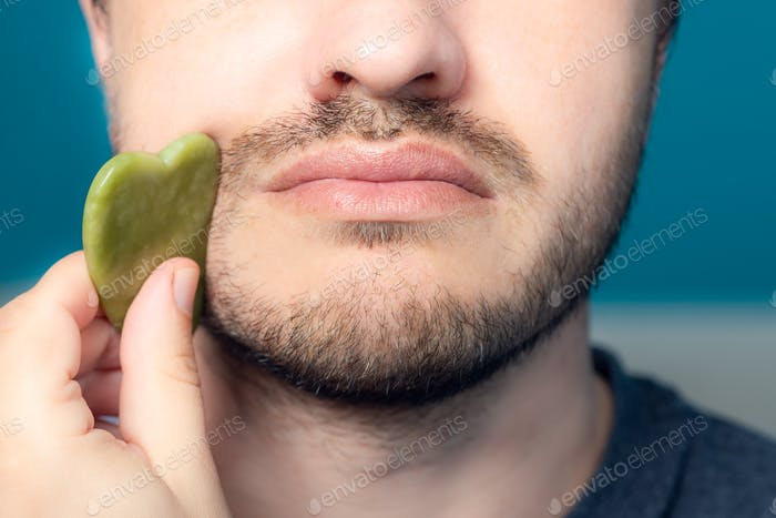 Bärtiger Mann verwendet Jade Gesicht Roller