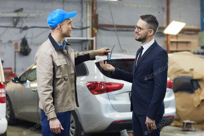 Reparaturmann gibt Autoschlüssel an Besitzer