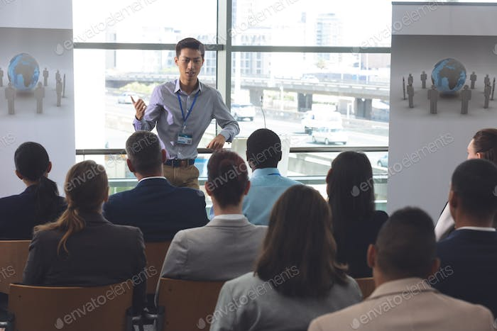 Businessman speaking in front of business professionals sitting at business seminar in office