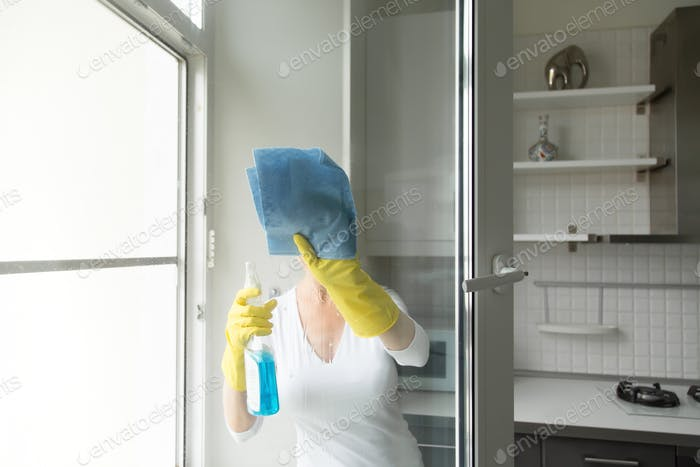 Young woman washing the windows
