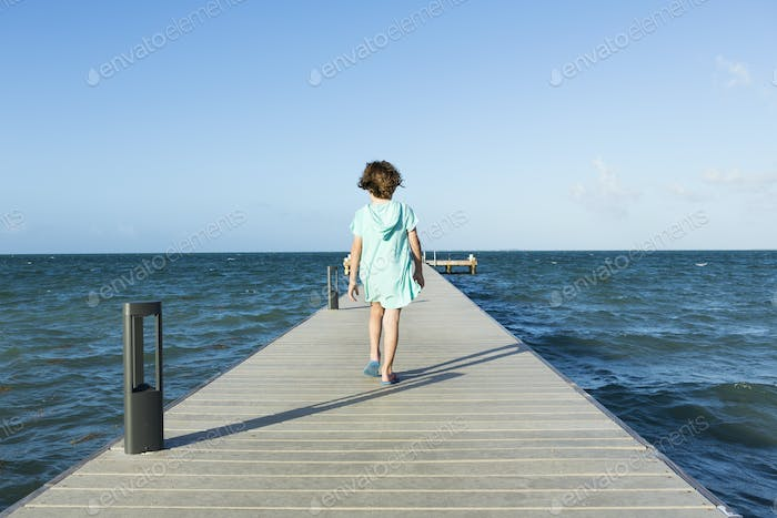 5 year old boy walking on pier, Grand Cayman Island