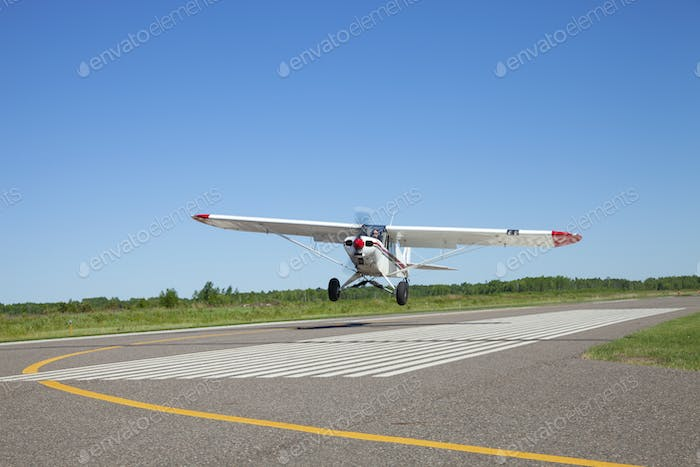 Small single engine airplane takes off from a municipal airfield in rural Minnesota