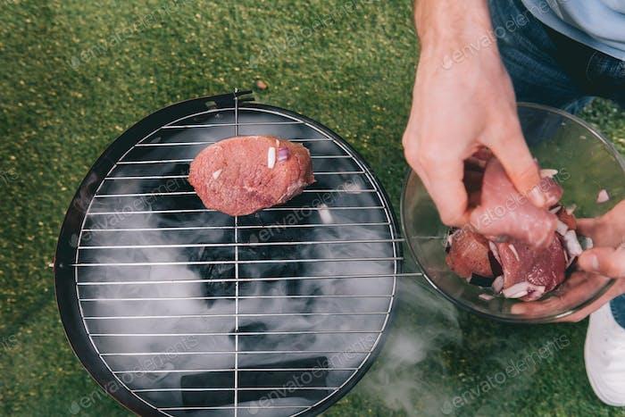 Mann Braten Fleisch mit Zwiebel auf Grill