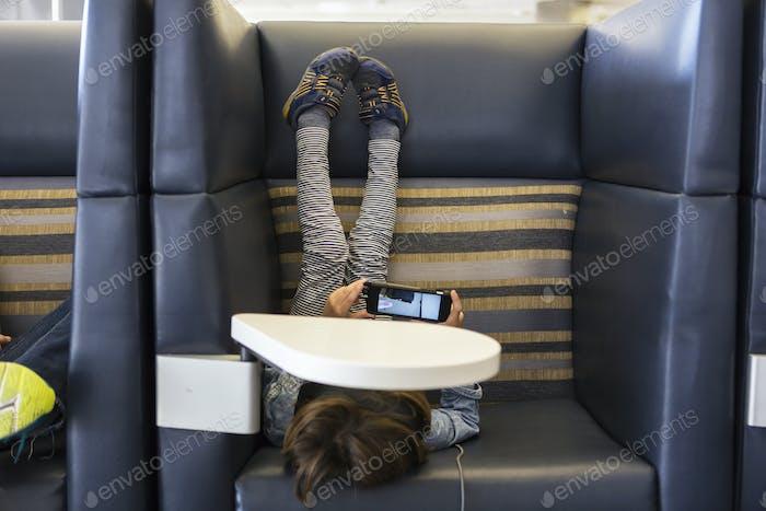 Ein Junge, der ein Smartphone in einer Abfluglounge am Flughafen benutzt.