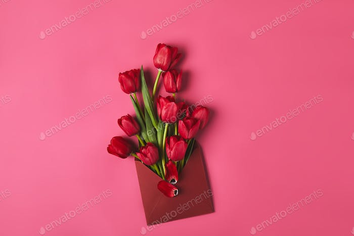 top view of red tulips in envelope on pink, mothers day concept