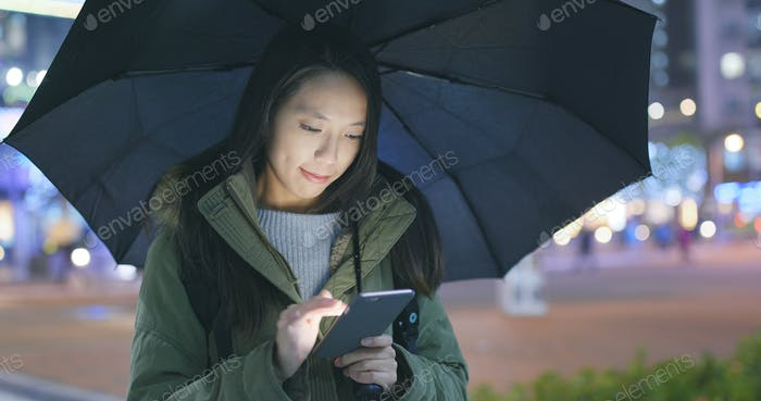 Woman look at mobile phone and bringing an umbrella
