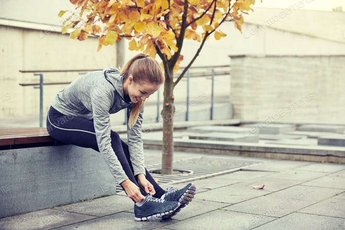 happy young sporty woman tying shoelaces outdoors