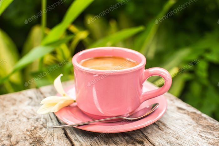 Pink cup of coffee on wooden table