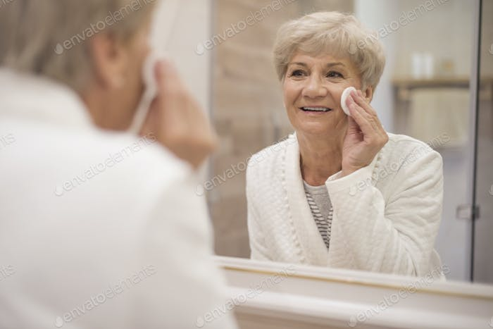 Senior woman standing in front of the mirror