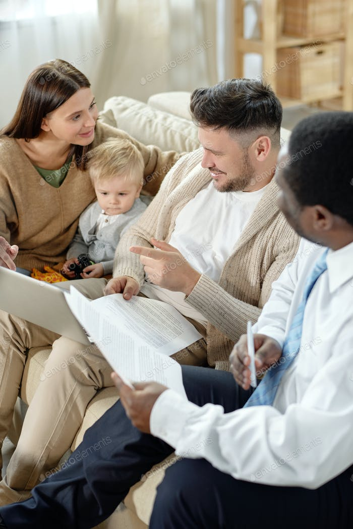 Cheerful family with black man discussing home loan