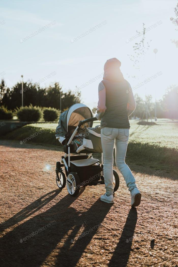 Junge Mutter mit einem Kinderwagen zu Fuß in einem Park. Konzept für Familie, Kind und Elternschaft.