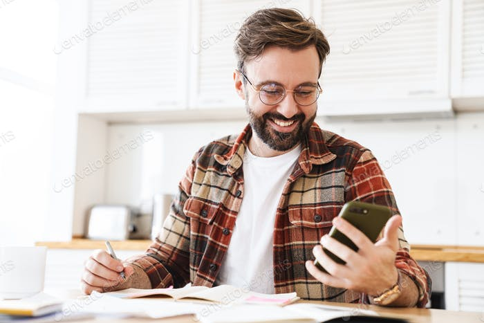 Portrait of excited bearded man using cellphone while working at home