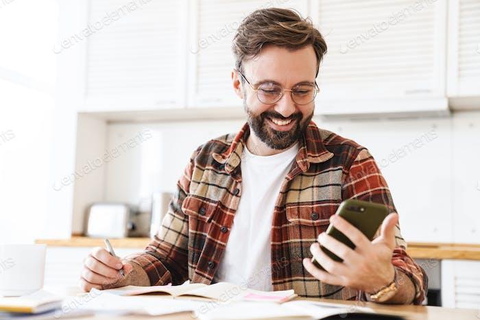 Porträt von aufgeregten bärtigen Mann mit Handy während der Arbeit zu Hause