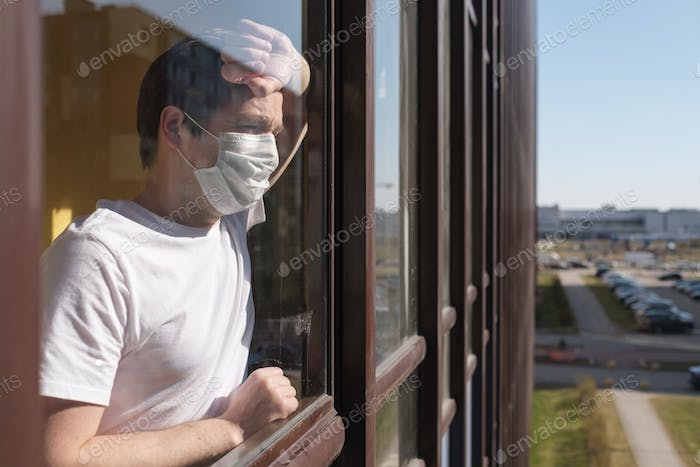 man with grippe looking through window and wearing mask protection