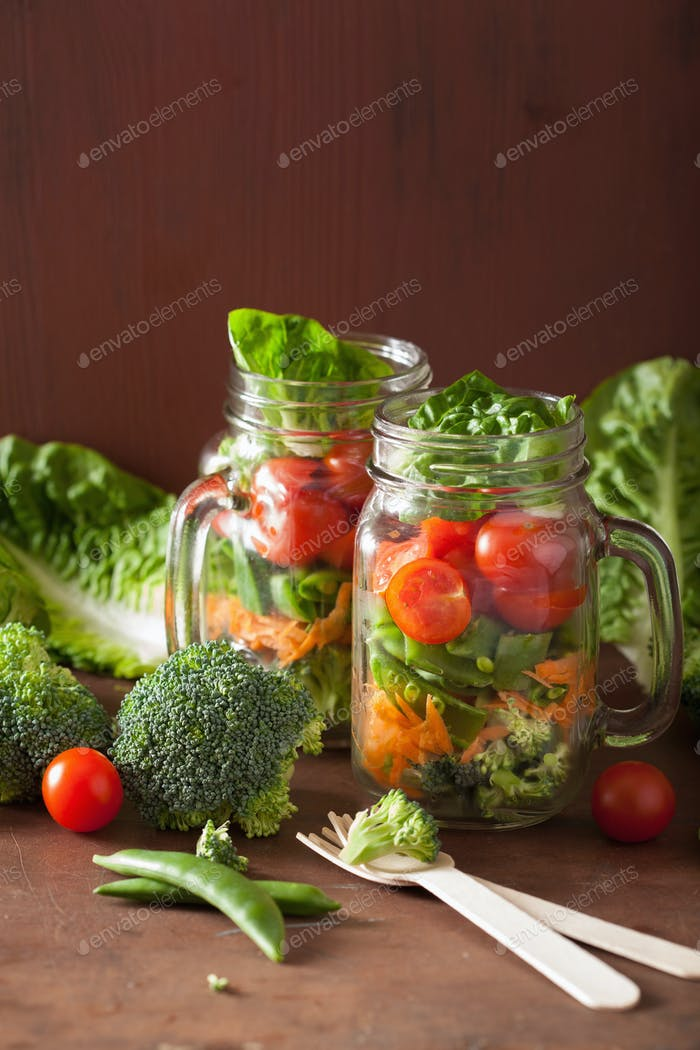 healthy vegetable salad in mason jar. tomato broccoli carrot pea