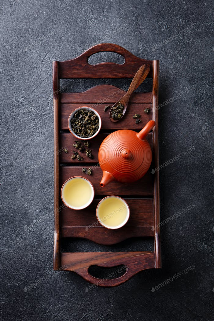 Green Tea Oolong in Teapot and Chawan Bowls, Cups on a Wooden Tray. Grey Background. Top View.