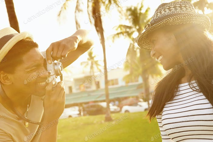 Man Taking Photograph Of Woman In Park