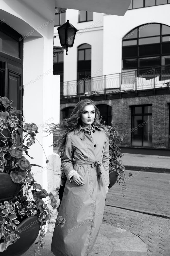 Girl standing on the street corner nearby the door