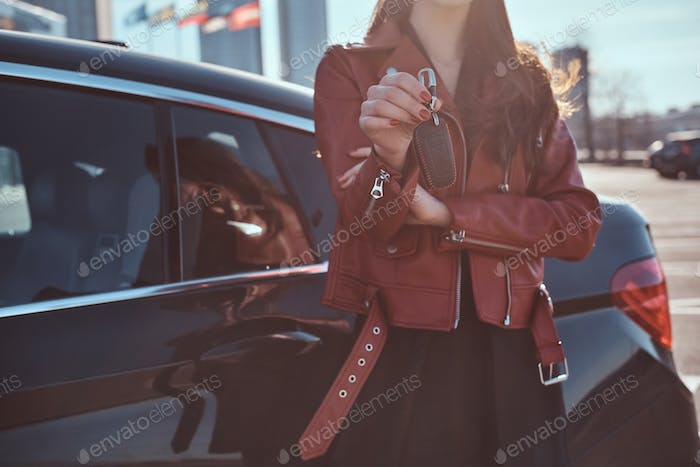 Women in red leather jacket just sold her car, which is behide her