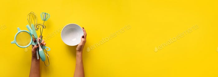 Woman hand holding kitchen utensils on yellow background. Baking tools - bowl, brush, whisk, spatula