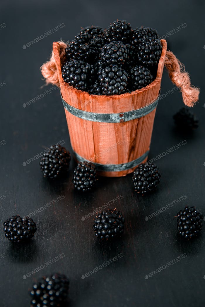Black raspberries in a wooden basket and on  table. Copy space.