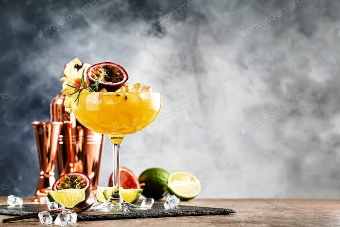 Alcoholic cocktail with fresh passion fruit with rosemary and ice