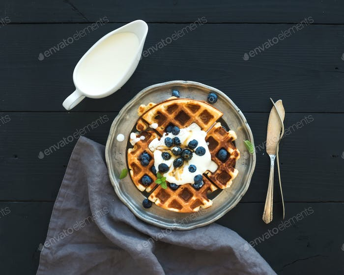 Soft Belgian waffles with blueberries, honey and whipped cream