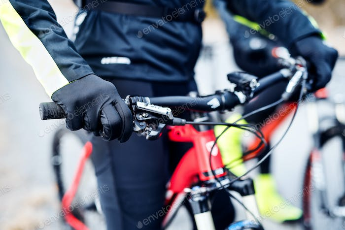 Midsection of mountain biker on road outdoors in winter