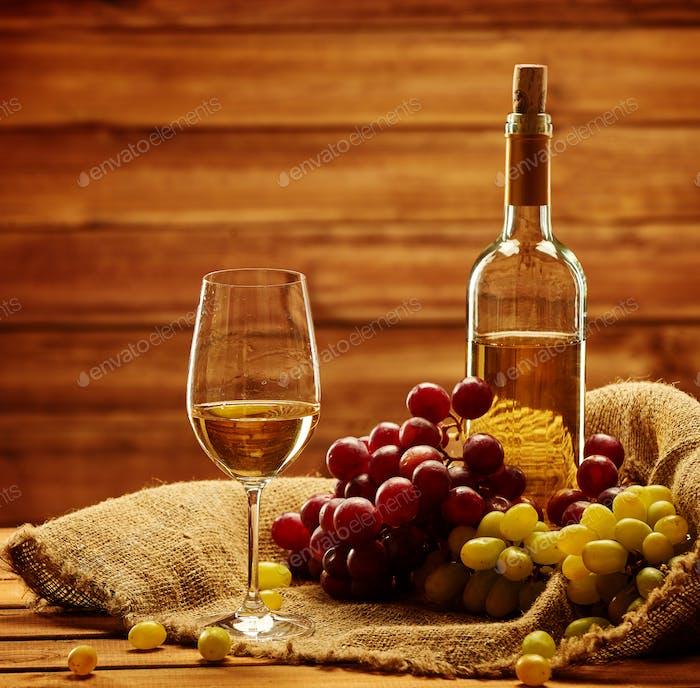 Flasche Weißwein, Glas und Traube auf einem Sack aus Holz interi